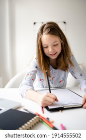 girl studying online at home looking at laptop at quarantine isolation period during pandemic. Home schooling. Social distancing. Online school test