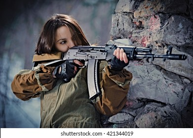 Girl styled as a soldier aims with her AK74