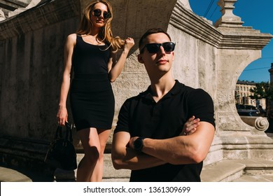 girl in a stylish black dress and sunglasses holds a bag in her hand. guy in black polo and sunglasses. couple near the moment