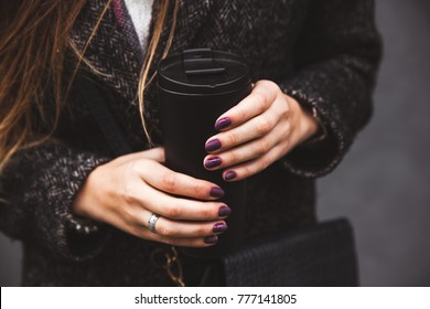 girl in stylish coat with beautiful manicure hand holding a black vacuum tumbler on a gray background a