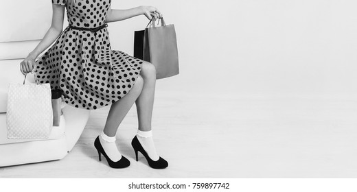 Girl in stylish dress and black shoes with shopping bags on a white background. Black Friday