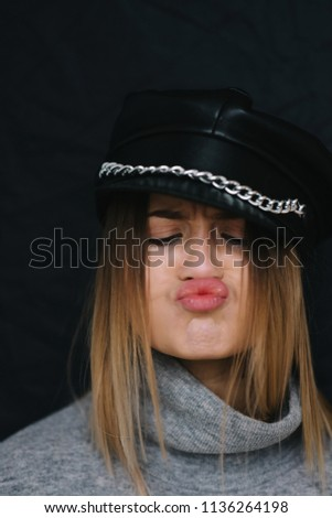 667146d3fd13b Girl in stylish leather cap making funny face. Trendy girl in rock style  wearing military