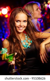 Girl in a stylish outfit standing at a bar counter holding a cocktail
