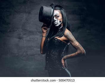 A girl in stylish top hat with skull make up and tattoo on arm. Halloween party.