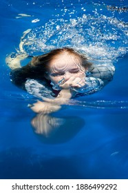 Girl submerged in a blue swimming pool