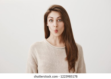 Girl sucking lips inside saw makeup artist will see jaw line. Portrait of attractive young caucasian woman with brunette hair puckering and looking with cute expression at camera, being over gray wall