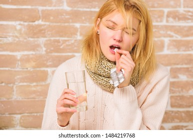 Girl suffer fever and take medicine. Headache and fever remedies. What to know about breaking fever. Take medications to reduce fever. Woman tousled hair scarf hold glass water and tablets blister.