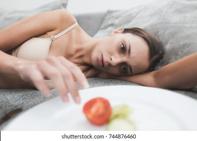 The girl suffering from anorexia. She is laying on a couch and trying to eat some food. The girl is looking at a plate with a slice of tomato and cucumber.