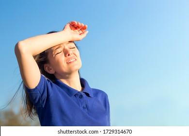 Girl suffering from pain, heat, woman with heatstroke. Having sunstroke at summer hot weather. Dangerous sun, girl under sunshine. Headache, feeling bad. Person holds hand on head. Coronavirus
