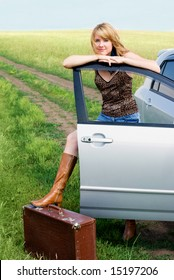 girl with a suitcase near her car