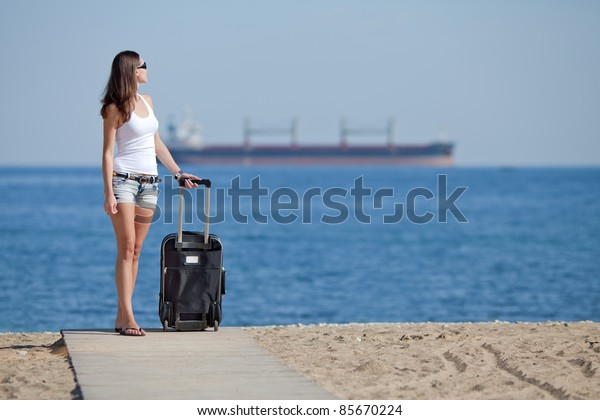 Girl with suitcase on the beach. Attractive young woman with rolling suitcase on the beach.