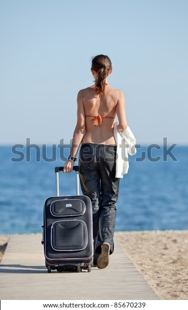 Girl with suitcase on the beach. Attractive young woman in orange bikini top and sunglasses with  rolling suitcase walks on the beach.