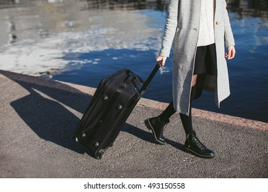 girl with a suitcase on the quay