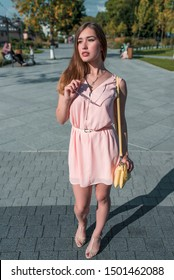 Girl in summer in city, pink dress sandals. In hands of sunglasses. The handbag yellow, view from front, background green spruce, tile pavers. A weekend break awaiting friends and girlfriends