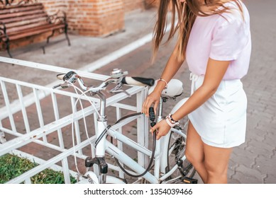 The girl in summer in city, puts castle on his bike, protection against theft, parking a bicycle in the city. Closes the cipher, locking the lock with a password, metal cable, to protect bike.