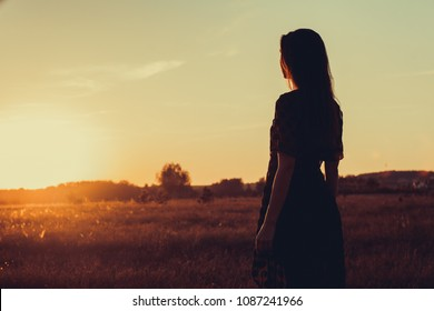 Girl in summer field on sunset background