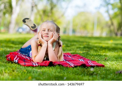 girl in a summer park lies on the rug on the grass