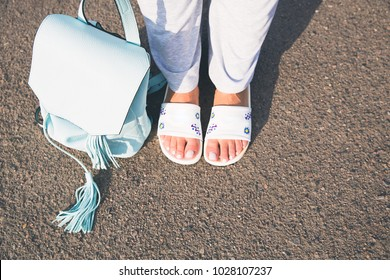 A girl in summer slippers and pants with a leather backpack in her hands. Summer street fashion look