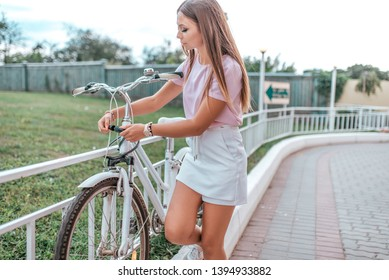 Girl in summer stands at bike, locks bike with cable. Picks up a password on the lock, against theft of a bicycle in parking lot. Bicycle rentals Cycling on the weekend. Active lifestyle.