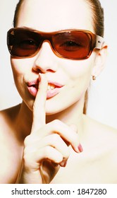 girl in sun glasses with finger on her lips