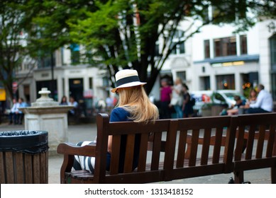 Girl in sun hat on the bench in the park. View from the back.