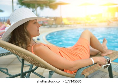 girl in a sun lounger by the pool