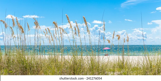 Girl sunbathing under pink umbrella on St. Pete beach in Florida, USA