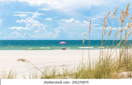 Girl sunbathing under pink umbrella on St. Pete beach in Florida, USA