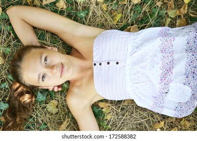 girl in a sundress lying on the grass