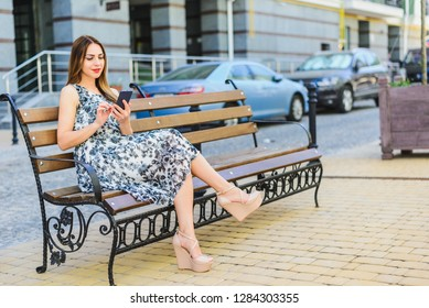 girl in a sundress sits on a bench. Horizontal frame