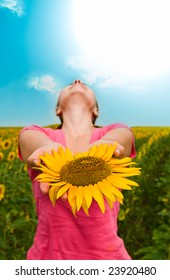 girl with a sunflower against the sky