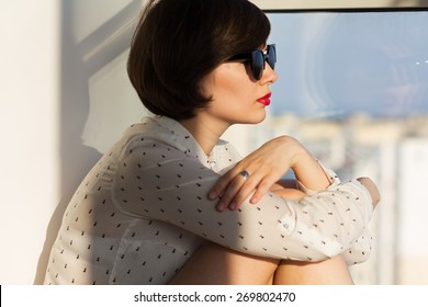 Girl with sunglasses daydreaming sitting by the window