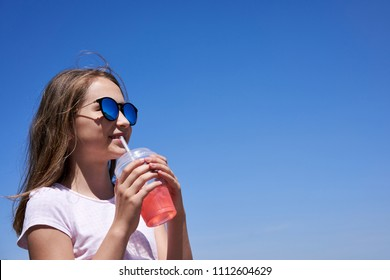 Girl in sunglasses drinking cold lemonade through a straw in summer sunny day, over blue sky