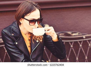 Girl in sunglasses drinks tasty coffee on brown terrace background, defocused. Woman with busy face spends time in cafe. Lady has cup of espresso during coffee break. Cafeteria and lunch time concept