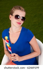 Girl with sunglasses and a lollipop sitting on a Swivel chair