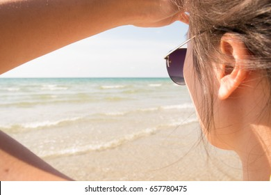 Girl with sunglasses look towards the ocean at the beach. Summer og holiday concept.