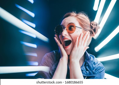 Girl in sunglasses looking surprised on neon background.
