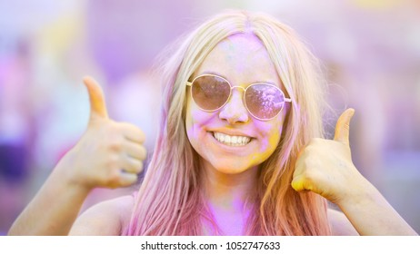 Girl in sunglasses making thumbs-up, enjoying fun atmosphere at color festival