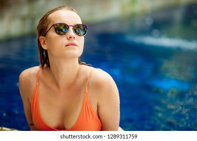Girl in sunglasses in an orange swimsuit sitting in the pool