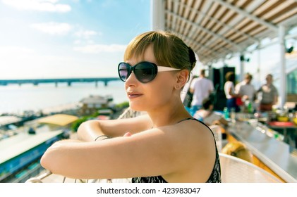 Girl in sunglasses standing and smiling on a sunny summer day