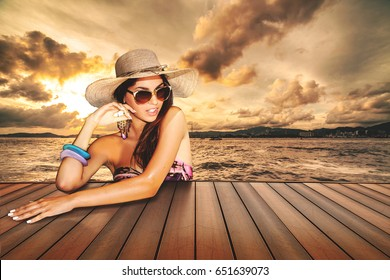 girl with sunglasses and straw hat on the pier restaurant