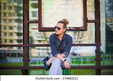 Girl in sunglasses waiting at the bus stop