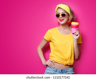 Girl in sunglasses and yellow t-shirt holding a red cup of coffee on pink background