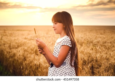 The girl at sunset costs in the field and holds wheat ears in hand