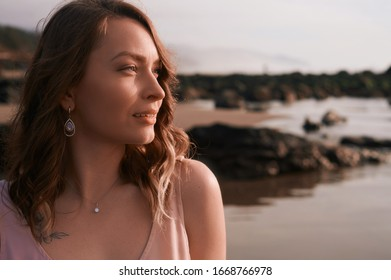 Girl at sunset on the beach, rocks and the ocean. Lifestyle, femininity, walks and relaxation. Horizontal photo. Oregon Cannon Beach.