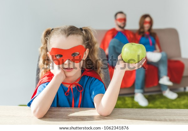 girl in superhero costume holding apple and looking at camera while super parents sitting behind