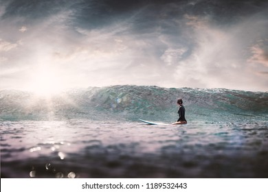 girl with surf board wait big ocean wave,dramatic sky and toning. lifestyle, people water sport lessons and beach swimming activity on summer vacation