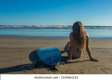 Girl with surfboard at the beach