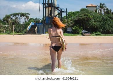 Girl surfing on the Indian Ocean, tropical Sri Lanka