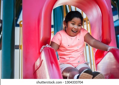 A girl with a surprised expression, looks down from the edge of a playground slide.